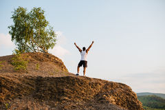 Black african american muscular athlete with hands raised to the sky on mountain top. Sport and freedom concept Royalty Free Stock Image