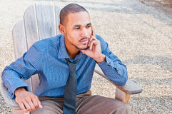 Black African American Professional Man. A young, handsome black african male wearing a dress shirt and tie is sitting, leaning forward, head supported by arm Royalty Free Stock Image