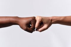 Black African American race female hand touching knuckles with white Caucasian woman in multiracial diversity stock photos