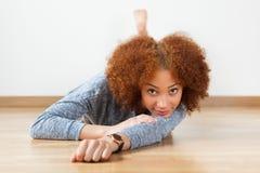 Black African American teenage girl lying down on the wood floor Stock Photography