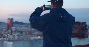 Black african american treveler makes a city panorama photos on smartphone Stock Image
