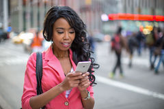 Black African American woman texting cellphone in city Stock Images