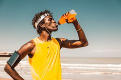 Running man at the beach drinking energy drink royalty free stock images