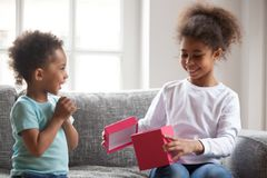 Black little brother presenting gift box for sister. Black African attractive little siblings sitting on couch at home. Lovely toddler brother presenting giving royalty free stock photos