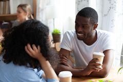 Black african couple drinking coffee sitting in cafe and talking. Rear view of mixed race female chatting with african american friend sitting together in cafe stock photos