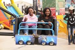 Black African female friends enjoying electronic roundabout ride Royalty Free Stock Photo