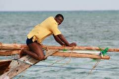 Black African fisherman, untie rigging sailing fishing boat. Zanzibar, Tanzania - February 18, 2008: Black African fisherman in yellow T-shirt, fixes rigging Royalty Free Stock Photos