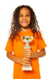 Black African girl with winners cup prize. Close portrait of happy African black girl with curly hair holding soccer winners cup prize and winners prize cup stock images