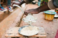 Black african hand grinding mais in old traditional way cooking outdoor in kitchen royalty free stock photography