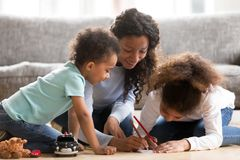 Black mother drawing with kids at home. Black African loving mother help to their children draw. Positive mom sitting with toddler son and preschool daughter on stock photo
