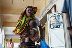 Black African mother with a baby in a sling. Royalty Free Stock Photos