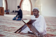 Black African Muslim Man Is Praying In The Mosque with open holy book of Koran Royalty Free Stock Photos