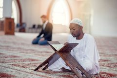 Black African Muslim Man Is Praying In The Mosque with open holy book of Koran Stock Images
