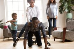 Father ride daughter on his back have a fun indoors stock photography