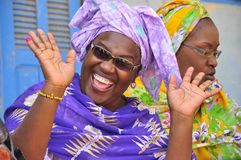 Black african women laughing. Colorfully dressed in traditional outfit. Senegal Stock Image