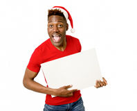 Black afro american man in Christmas Santa hat smiling happy showing blank billboard copy space Royalty Free Stock Images