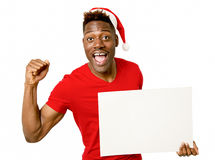 Black afro american man in Christmas Santa hat smiling happy showing blank billboard copy space. Young attractive black afro american man in Christmas Santa hat royalty free stock images