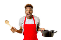 Black afro american man home cook in chef apron cooking pot and Royalty Free Stock Photo