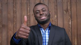 Black afro american smiling man shows gesture thumb up on dark wood background. Afro american businessman in shirt and suit jacket. Black smiling man shows stock video