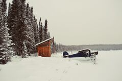 Black Aircraft Beside Brown Bunk House on Snowy Place Royalty Free Stock Images