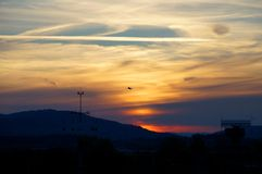 Black airplane silhouette in front of a reddish sunset sky. Black silhouette of an airplane taking off in front of cirrus clouds colored by the setting sun stock image