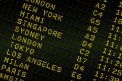 Black airport departures board with yellow text Royalty Free Stock Photo