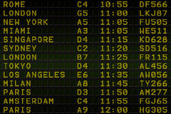 Black airport departures board with yellow text Stock Photos