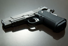 Black Airsoft Pistol. On reflective surface Royalty Free Stock Image