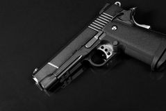Black Airsoft Pistol. On reflective surface Stock Image