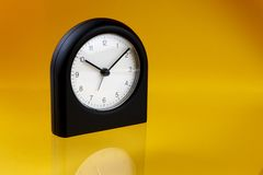 Black alarm clock. Modern, black alarm clock shot on yellow-orange background with reflection and space for copy Royalty Free Stock Images