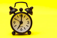Black Alarm Clock. On yellow background - seven o'clock Royalty Free Stock Images