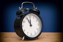 Black alarm clock against blue background Royalty Free Stock Photos