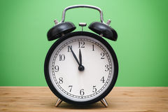 Black alarm clock against green background Royalty Free Stock Photos
