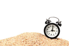 Black alarm clock on the beach. With white background Stock Image