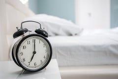 Awaking. Black alarm clock and bed royalty free stock image
