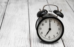 Black alarm clock. On a old white wooden  background Stock Photos