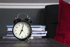 Black alarm clock on a black and white striped napkin showing 7 o'clock on a bedside table Royalty Free Stock Photos