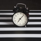 Black alarm clock on a black and white striped napkin showing 7 o`clock on a bedside table Royalty Free Stock Images