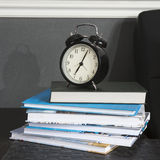 Black alarm clock on a black and white striped napkin showing 7 o`clock on a bedside table Stock Photo