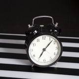 Black alarm clock on a black and white striped napkin showing 7 o`clock on a bedside table Stock Images