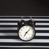 Black alarm clock on a black and white striped napkin showing 7 o'clock on a bedside table Royalty Free Stock Photo