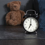 Black alarm clock on a black and white striped napkin showing 7 o'clock on a bedside table Stock Photo