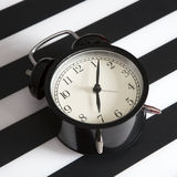 Black alarm clock on a black and white striped napkin showing 7 o'clock on a bedside table Stock Images
