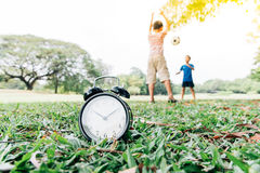 Black alarm clock and boy play in the park Royalty Free Stock Images
