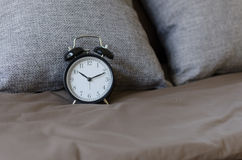 Black alarm clock on brown bed with grey pillow Royalty Free Stock Photography
