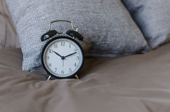 Black alarm clock on brown bed with grey pillow Stock Photo