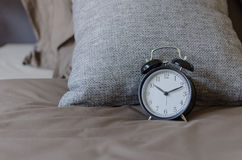 Black alarm clock on brown bed with grey pillow Royalty Free Stock Images