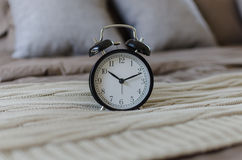 Black alarm clock on brown bed with grey pillow Royalty Free Stock Image