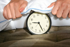 Black alarm clock covered by a white pillow Stock Image