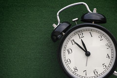 Black alarm clock on a green background Stock Images